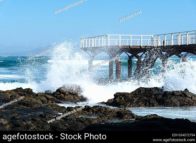 Waves breaking against pier on the beach of Corralejo at morning against blue sky