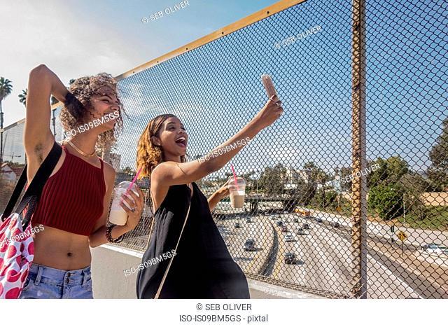 Two young women taking selfie on highway footbridge, Los Angeles, California, USA
