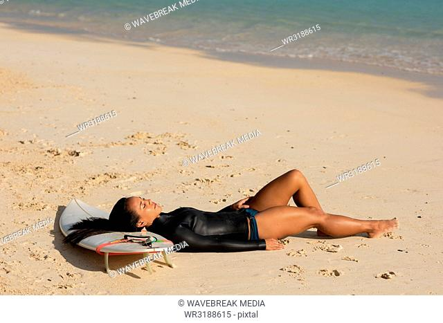 Woman sleeping on surfboard in the beach