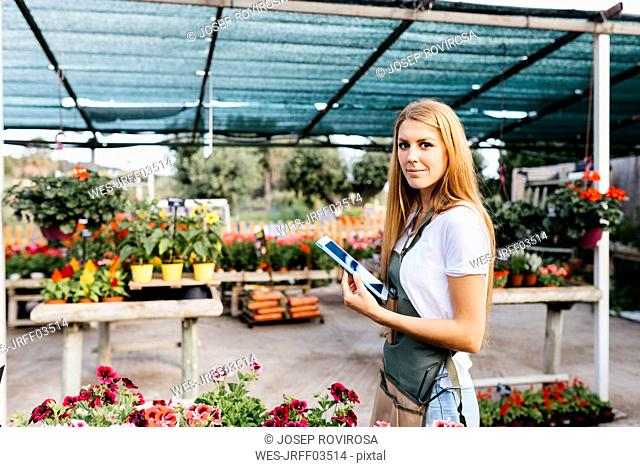 Portrait of a smiling female worker in a garden center holding a tablet