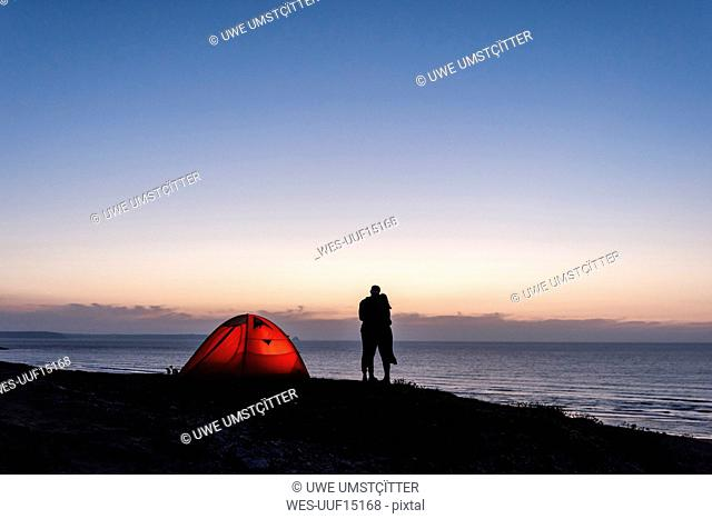 Romantic couple camping on the beach, kissing in twilight