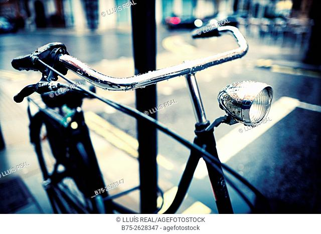 Close-up of the handlebar and lamp of a Dutch bicycle parked on a lamppost, on a rainy day. London, England, UK, Europe