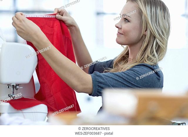 Young woman working with measuring tape and sewing machine