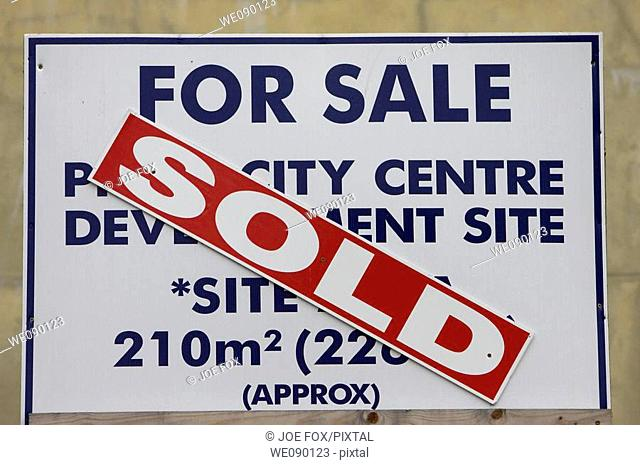 sold notice put across for sale sign in city centre environment