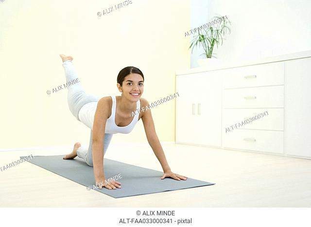 Woman down on all fours, exercising, smiling at camera