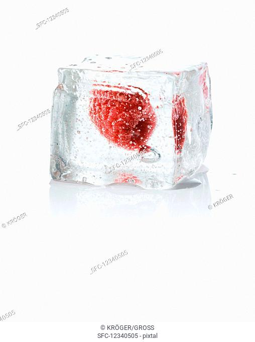An ice cube with a rapsberry