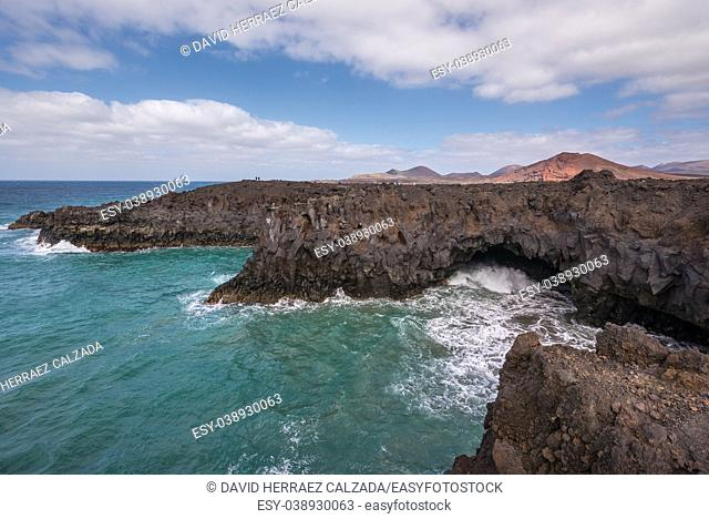 Lanzarote landscape. Los Hervideros coastline, lava caves, cliffs and wavy ocean. Unidentifiable tourist are in the background