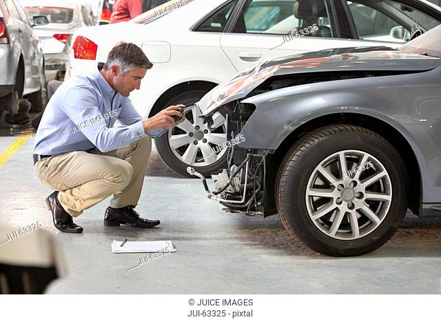 Insurance assessor inspecting damaged vehicle and taking photograph