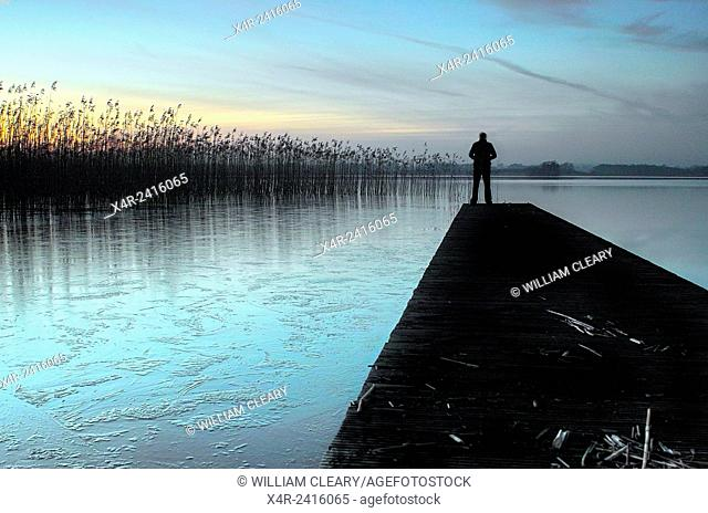 Man standing on jetty, late evening Lough Ennell, County Westmeath, Ireland