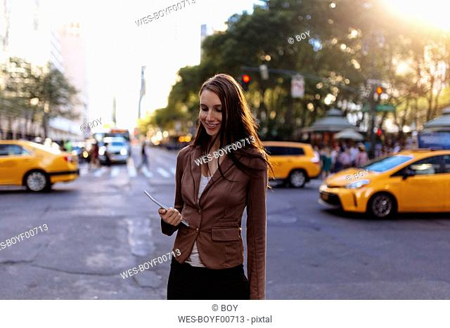 USA, New York, Manhattan, smiling young businesswoman with tablet on the street