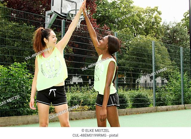 Women cheering on basketball court
