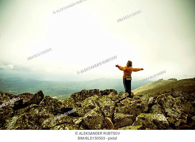 Caucasian hiker with arms outstretched on rocky hilltop