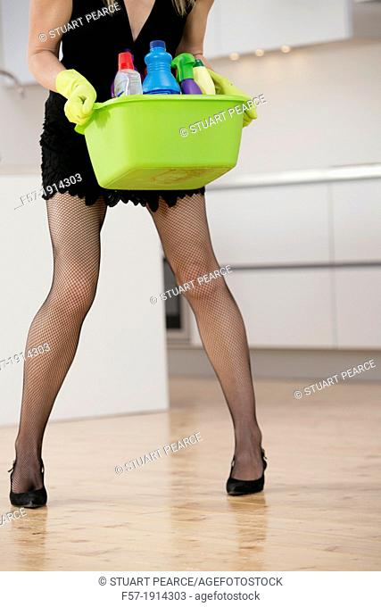 Detail of a sexy young woman with a bucket of cleaning products in the kitchen wearing high heels and rubber gloves