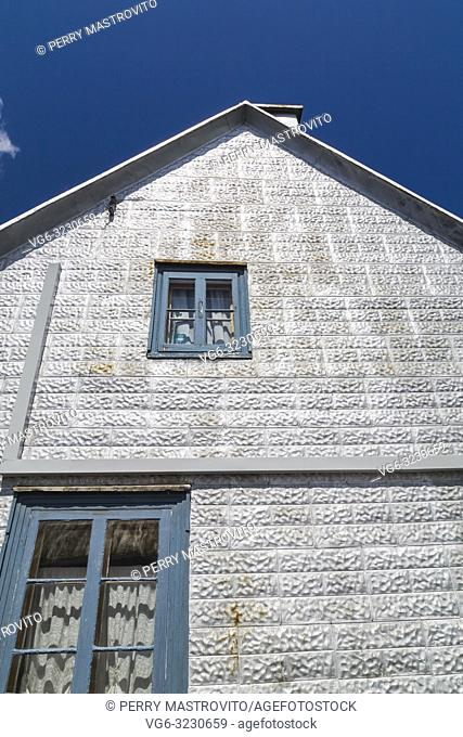 Side wall with windows on old 1839 silver metalic embossed tile with blue and white trim exterior finish Canadiana cottage style home