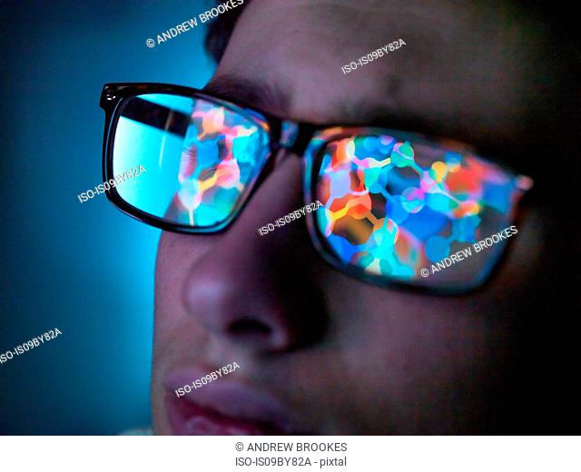 Biotechnology research, computer screen reflection in spectacles of new molecular formula in laboratory, close up of face