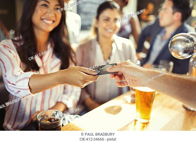 Smiling woman paying bartender with credit card at bar