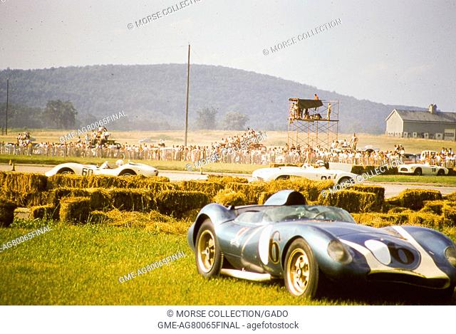 View of Lance Reventlow's Mk, August 17, 1958. I Scarab race car No. 6, seen at lower right with a dented front end following a crash into the hay bales lining...