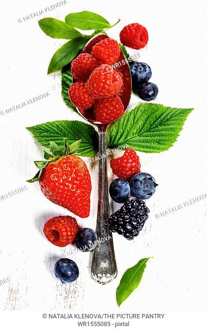 Berries with spoon on Wooden Background. Strawberries, Raspberries and Blueberries. Health, Diet, Gardening, Harvest Concept