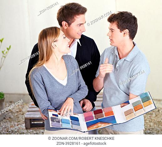 Paar schaut verschiedene Teppichmuster beim Fußbodenleger an