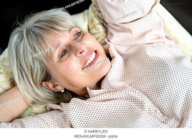 Happy mature woman lying down relaxing