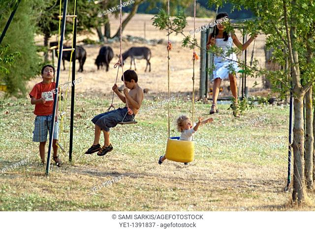 Four children playing on a swingset, Carcassonne, France