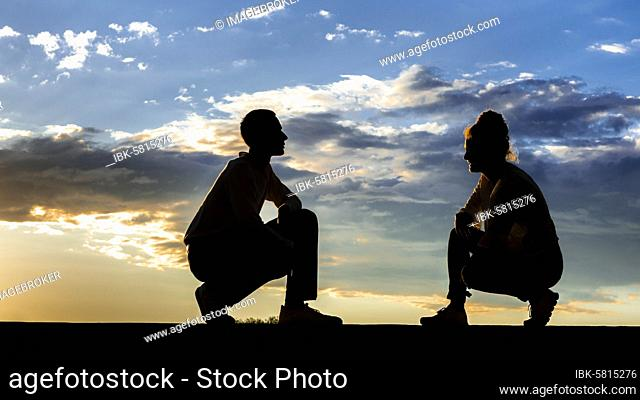 Man, 21 years, woman, 23 years, silo hut, sitting, in the sunset, Remstal, Baden-Württemberg, Germany, Europe