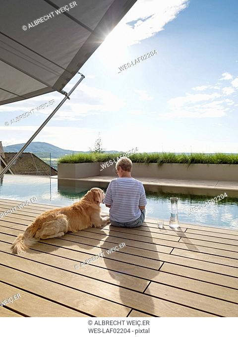 Senior woman sitting with dog at the poolside