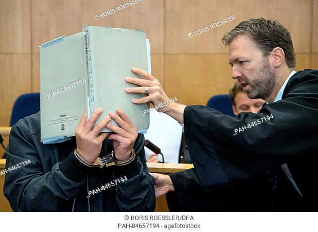 Torsten Fuchs, a lawyer representing Yejun G., one of the defendants in a murder case, guides his client into the courtroom while covering his face with a...
