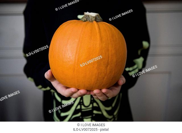 Child holding an orange Hallowe'en pumpkin