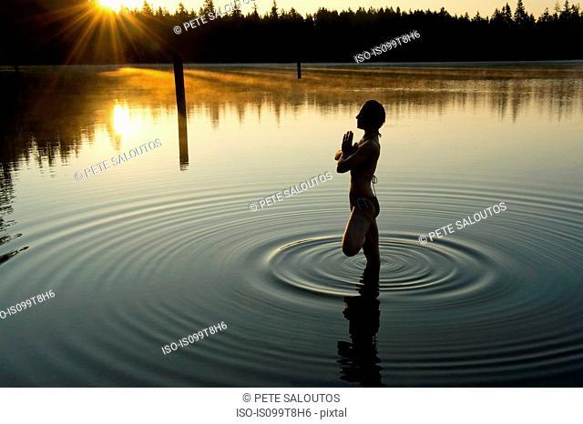 Woman meditating in calm lake