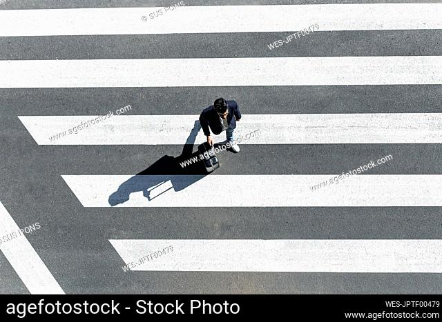 Man on zebra crossing pushing his trolley bag, top view
