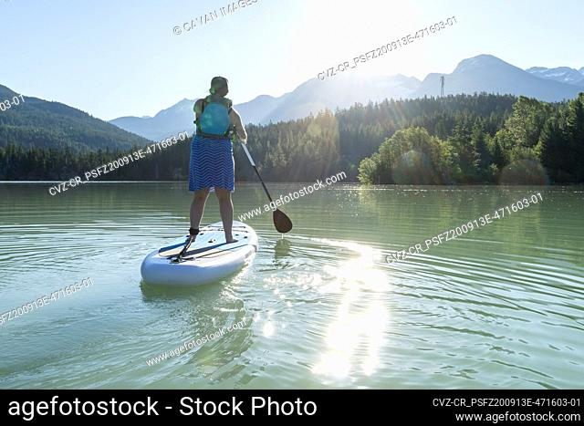 Back view of barefoot woman in dress and life vest riding SUP board on calm lake water on sunny summer day in mountains in British Columbia, Canada