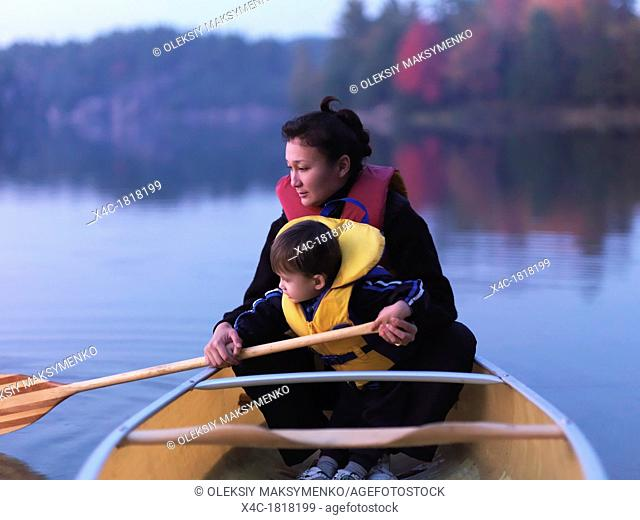 Mother with a three year old boy learning to paddle a canoe, fall nature scenery  Kilarney, Ontario, Canada