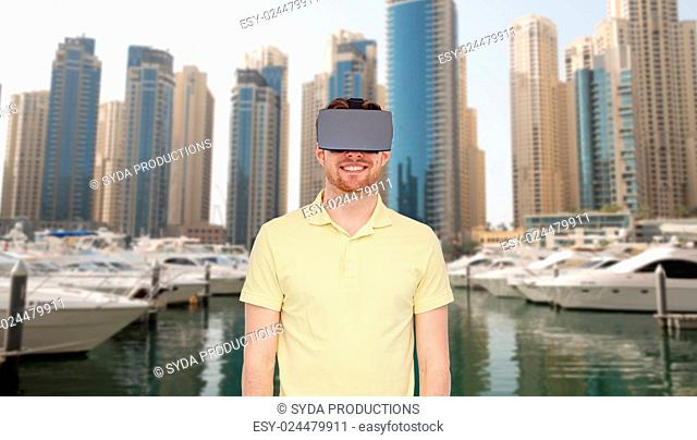 3d technology, virtual reality, travel, entertainment and people concept - happy young man with virtual reality headset or 3d glasses over dubai city street...