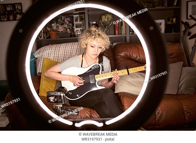 Female blogger playing guitar in living room