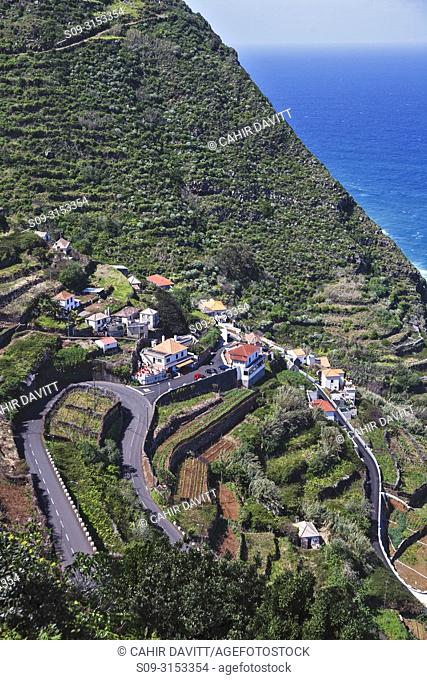 Aerial view of the suburb of Lanceiros, Porto Moniz, located on the North West Coast of Madeira with a twisty mountain road and terraced hillsides, Lanceiros