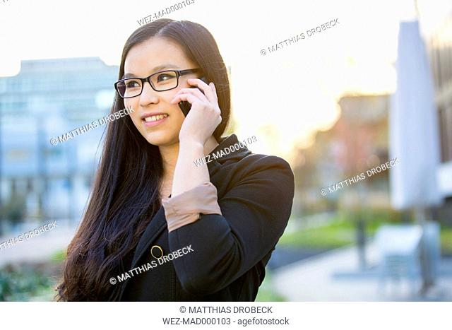 Portrait of young businesswoman telephoning with smartphone