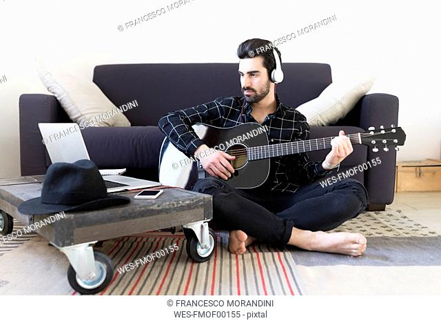 Young man at home playing guitar and wearing headphones connected to laptop