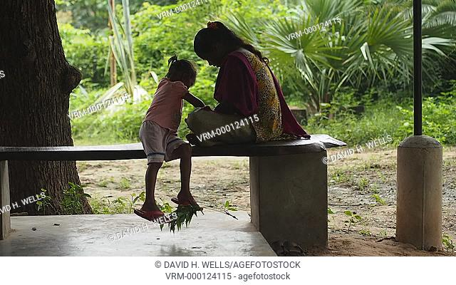 Girls sitting on stone bench on farm near Ahmedabad, Gujarat, India
