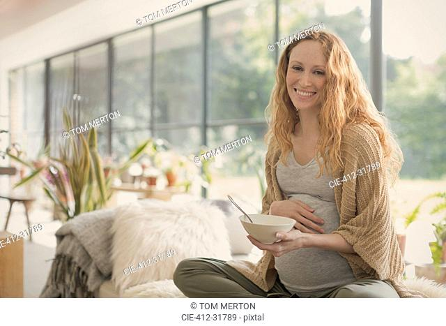 Portrait smiling pregnant woman eating ice cream