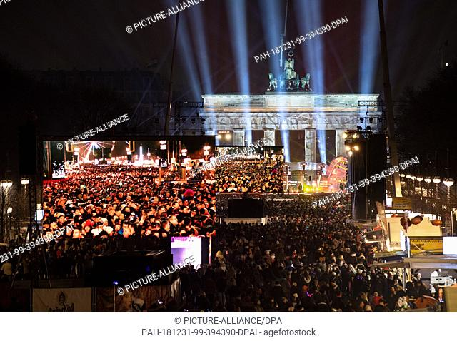 31 December 2018, Berlin: Thousands of spectators watch Germany's biggest New Year's Eve party at the Brandenburg Gate. Photo: Monika...