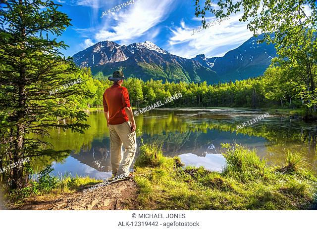 Hiker standing next to Dew Pond in the Chugach State Park near Eagle River, Southcentral Alaska, summer