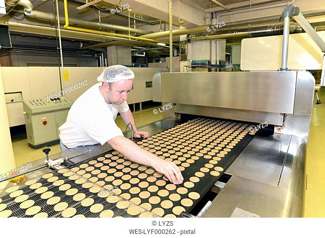 Germany, Saxony-Anhalt, man controlling cookies in a baking factory