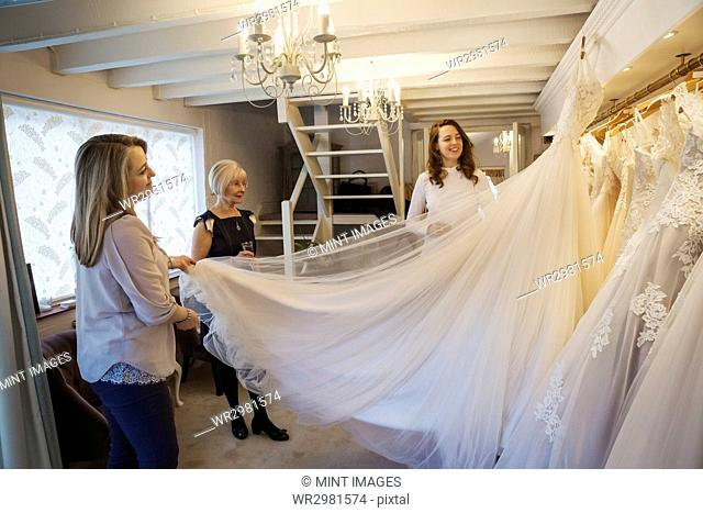 Three women in a wedding dress shop, one holding out the full skirt of a bridal gown