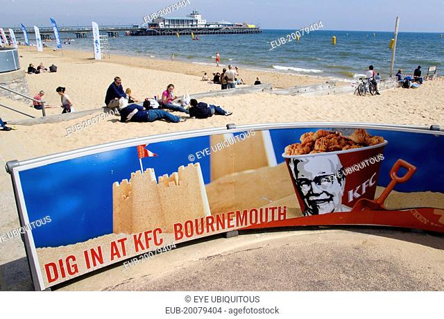 Tourists playing in the sand and watching speedboat races off the West Beach beside the pier. A KFC advertising board in the foreground
