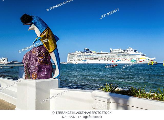 Decorative sculptures along the malecon with cruise ships in the port of Cozumel, Mexico