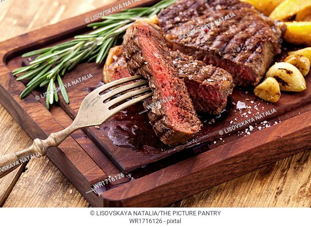 Sliced medium rare grilled Beef steak Ribeye with roasted potato wedges on cutting board on wooden background