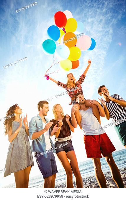 Friends dancing on sand with balloon