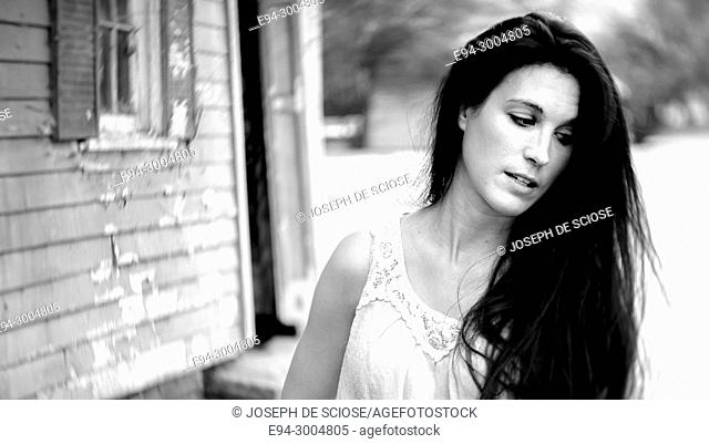 A casually dressed 39 year old brunette woman looking away from the camera, with an old house in the background, black & white