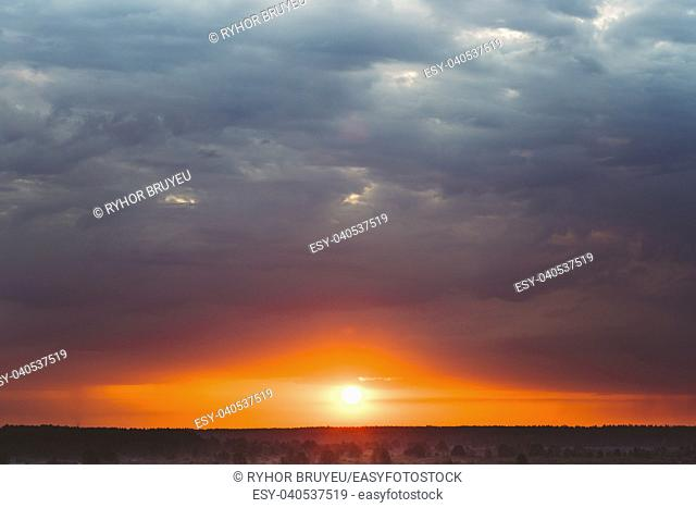 Dark Sky, Blue, Yellow And Orange Colors Sunset (Sunrise). Sun over forest horizon